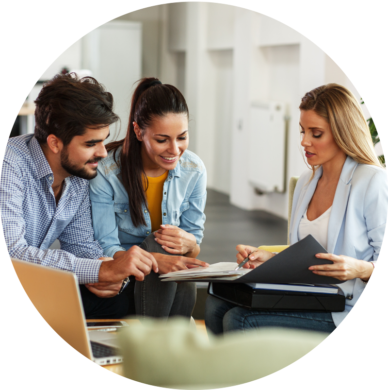 Focused-and-happy-smiling-couple-with-realtor-going-over-papers