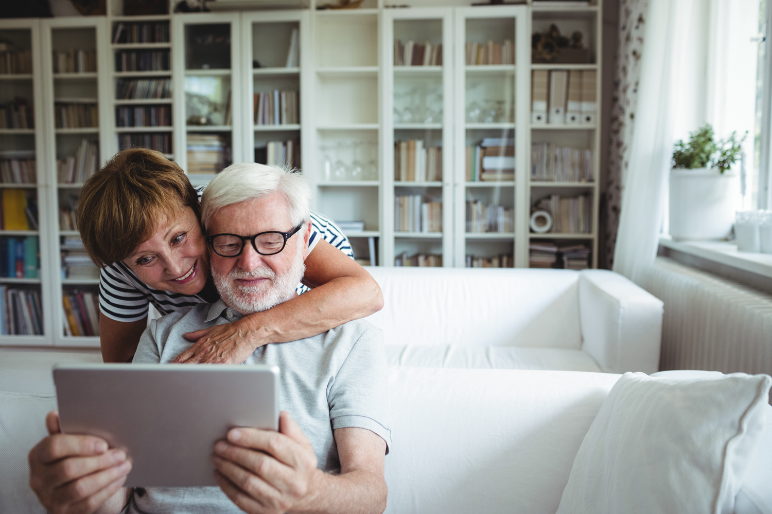 Happy-Couple-in-front-of-bookshelf-looking-at-laptop-smiling