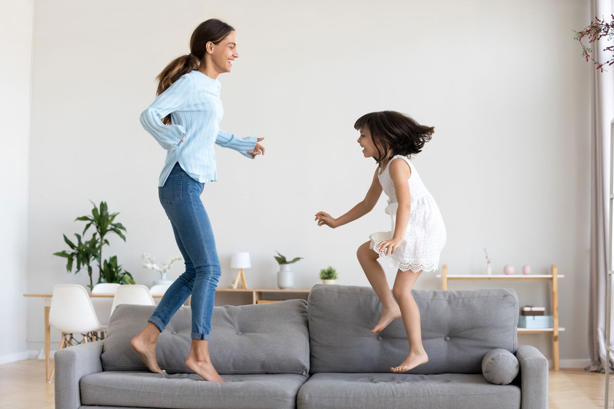 Mother-and-Daughter-jumping-on-couch-at-home-excited